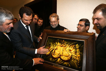 "Bashar al-Assad receiving a big gleaming golden ""Allah"" from Ali Larijani, the speaker of Iran's Parliament after a meeting at the Presidential Palace in Damascus, December 2014"