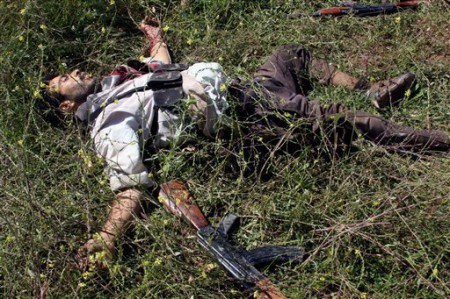 The body of a gunman killed during clashes with Iraqi security forces lies on the ground in Hawija - AP Photo