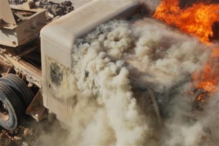 An Iraqi army military vehicle burns near a demonstration site in Ramadi, Iraq - AP Photo