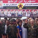Ali Kayali presiding over PFLI/Syrian Resistance ceremonies at the funeral of Mohammed Darrar Jammo, July 2013. Sheikh Mowaffaq Ghazal stands next to him.