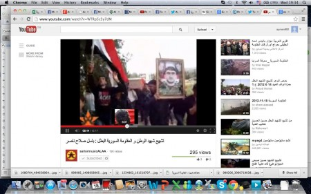 Mourners hold Basil's portrait and wave the flag of Syria