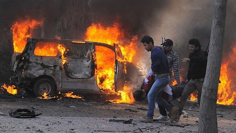 Service burns behind Syrian security agents carrying a man at site of car bombing near the Baath party headquarters and Russian Embassy in central Damascus, Feb 21, 2013, SANA-AP
