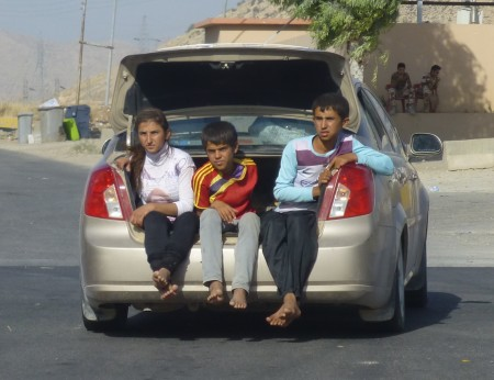 Yazidis flee Sinjar in overcrowded car, barefoot—photo: Matthew Barber/Syria Comment
