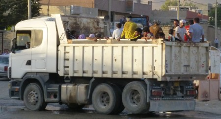 Yazidi refugees from Sinjar riding in dumptruck in Shariya